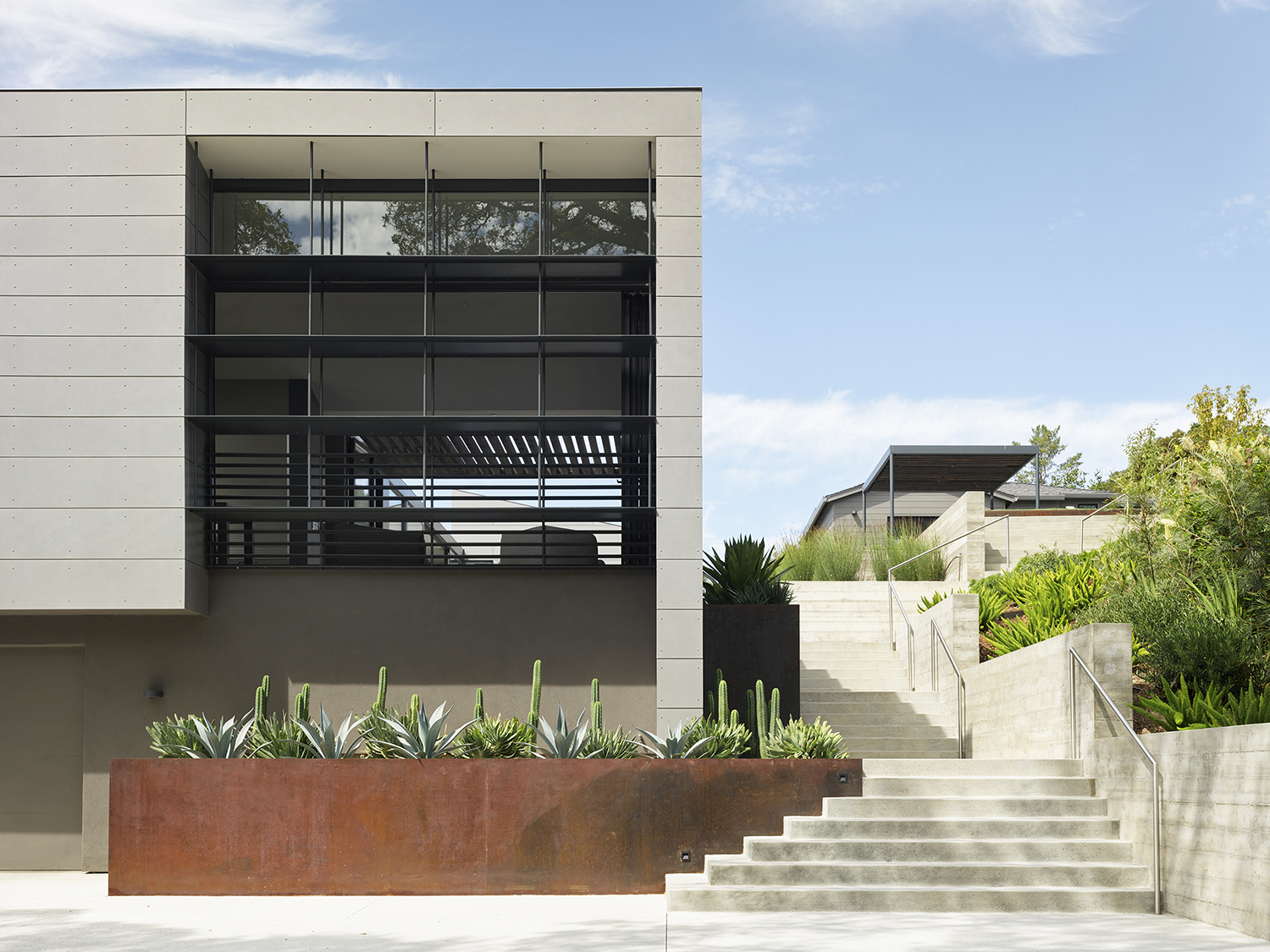 Ross Hillside modern home outside view of the front of the house with stairs on the side