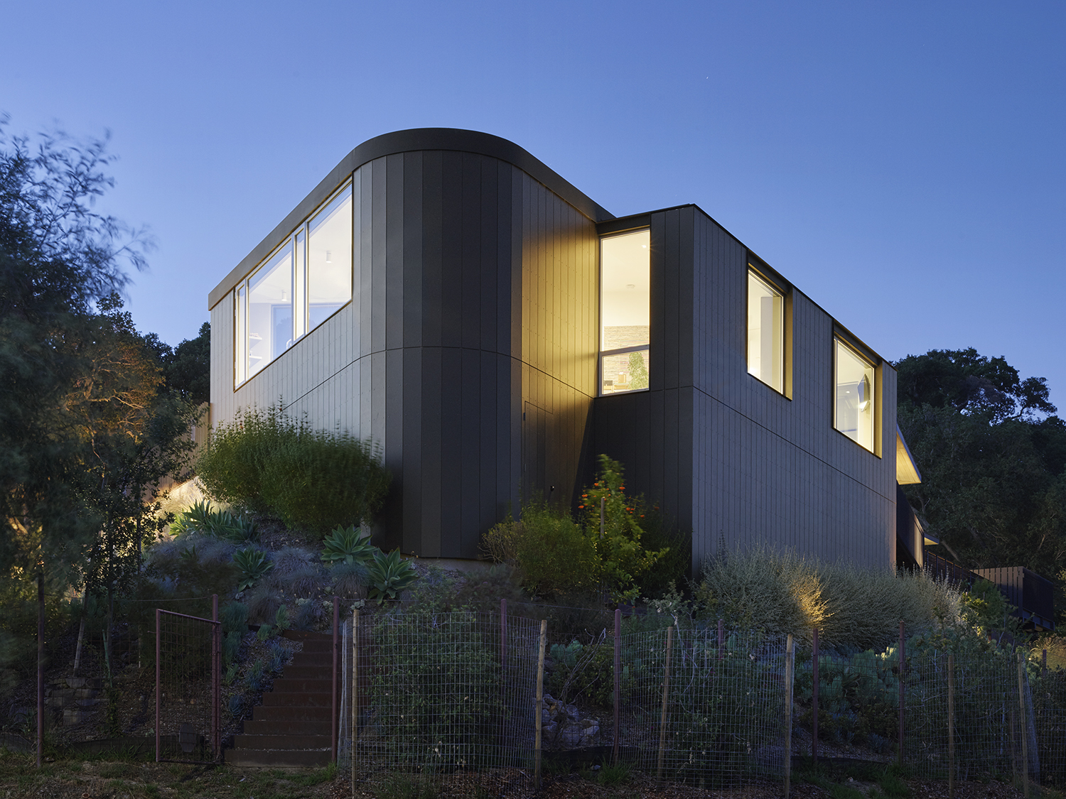 Herspring House renovated in Kentfield California, outside view at night, illuminated windows