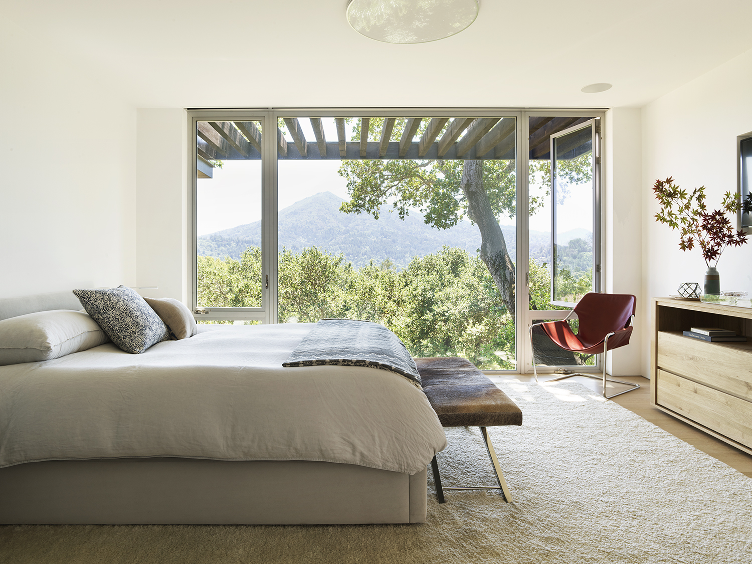 Herspring House renovated in Kentfield California, inside view of bedroom with bed, furniture and floor to ceiling windows.