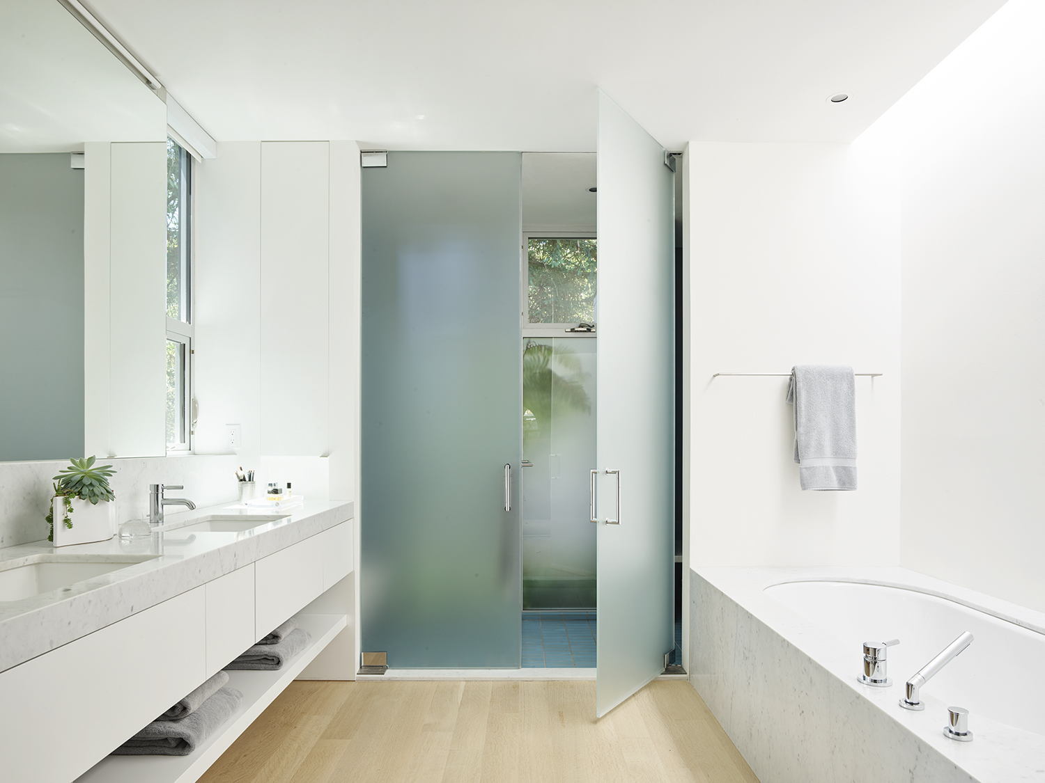 Herspring House renovated in Kentfield California, inside view of bathroom with bathtub, shower, sink and mirrors