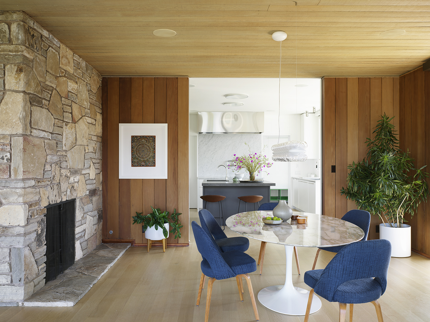 Herspring House renovated in Kentfield California, inside view of living space, marble round table with blue chairs, fireplace on the left, kitchen on the back.