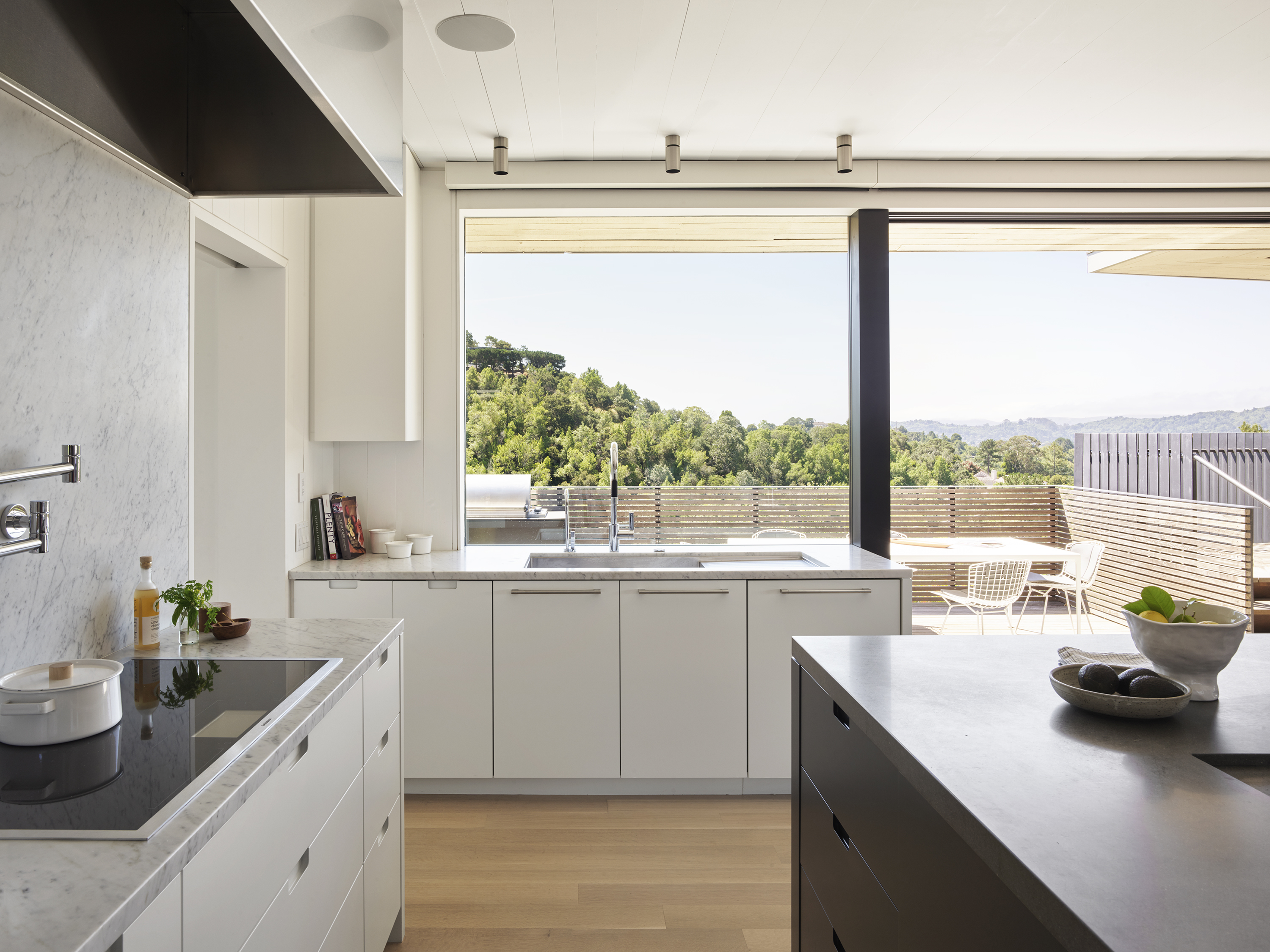Herspring House renovated in Kentfield California, inside view of kitchen area, sink, kitchen cabinets, kitchen drawers, kitchen island and view of terrace.